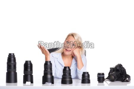 genervte fotografin sitzt vor verschiedenen objektiven