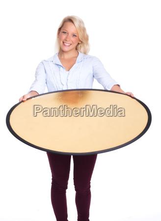 blond woman holding a photograph reflector