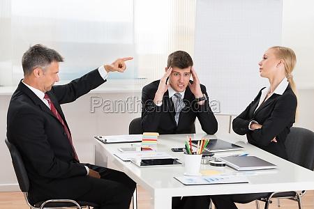 geschaeftsmann streitet mit seinen zwei mitarbeitern