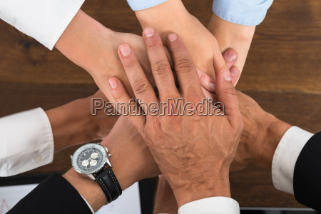 businesspeople hands stacking over each other