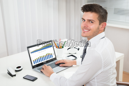 businessman working with graph on laptop