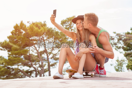 happy couple with sitting on skateboard