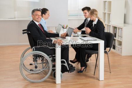 disabled businessman with colleagues in office