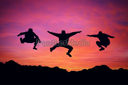 three boys jump over a mountain