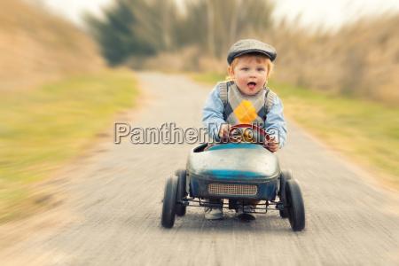 lachender junge mit seinem tretauto