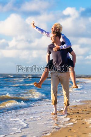 mann traegt frau huckepack am strand