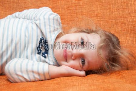 the three year cheerful girl lying