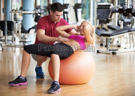 junge sportliche frau mit trainer uebung