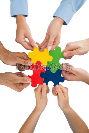 people hands holding jigsaw pieces