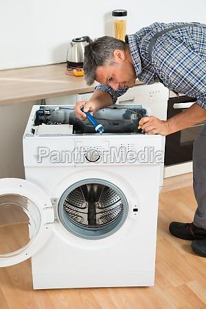 handyman check waschmaschine mit taschenlampe