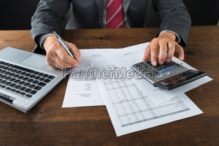 midsection of businessman checking bills at