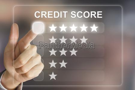 business hand pushing credit score on
