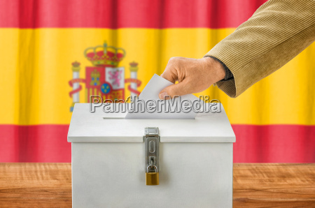 mann wirft stimmzettel in wahlurne