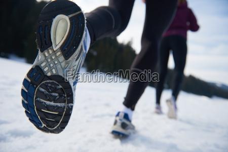 paar joggen draussen auf schnee