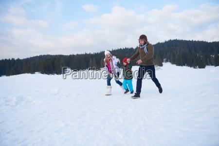 glueckliche familie die im winter im