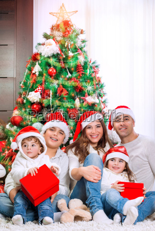 glueckliche familie nahe weihnachtsbaum