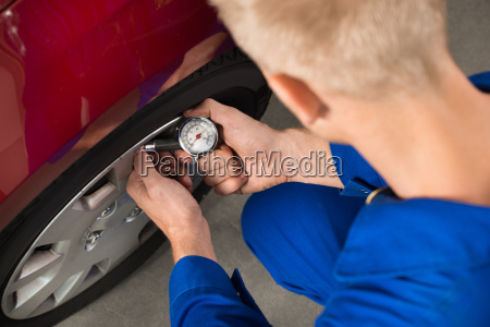 mechanic checking air pressure level in