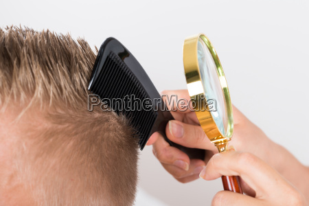 doctor looking at patients hair through