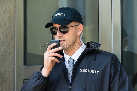 security guard using walkie talkie radio