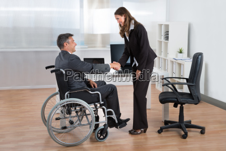 businesswoman shaking hands with businessman on