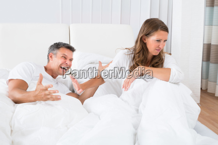 couple disputing on bed