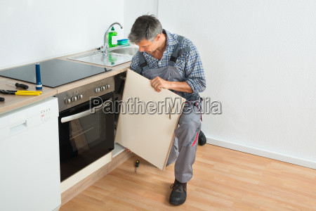 handyman fixing sink tuer in der