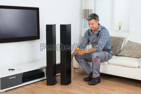 techniker pruefen tv sprecher mit multimeter