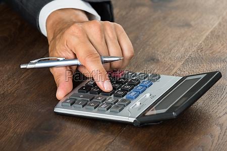 businessman using calculator at desk