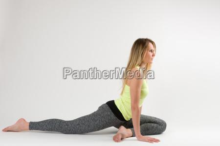 blonde frau die yoga und stretching