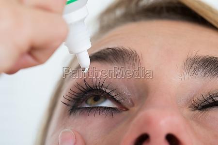 woman applying eye drop over white