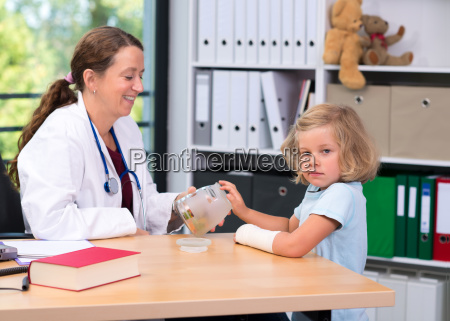 female pediatrician bandaging the arm of