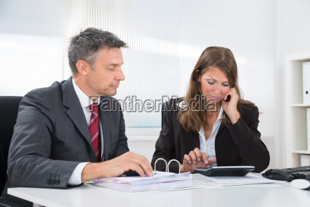 two businesspeople doing accounting at desk