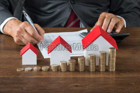 businessman calculating tax by house models
