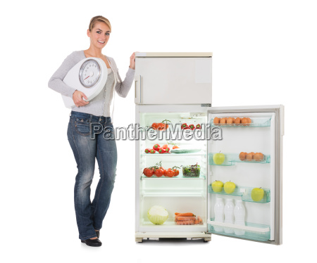 woman holding weighing scale while standing