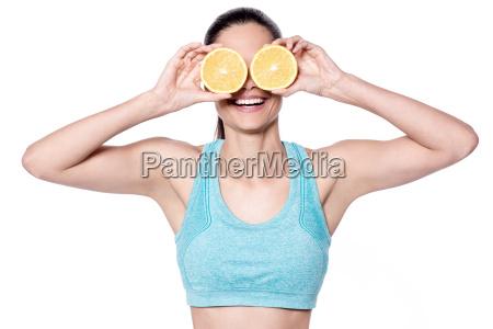 cheerful lady showing sliced orange