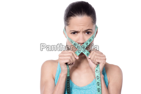 woman covering mouth with measuring tape