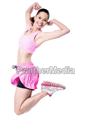 fit young woman jumping high in