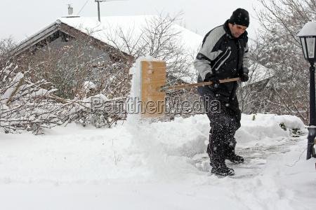 ein mann raeumt bei starkem schneefall