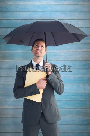 composite image of businessman sheltering under