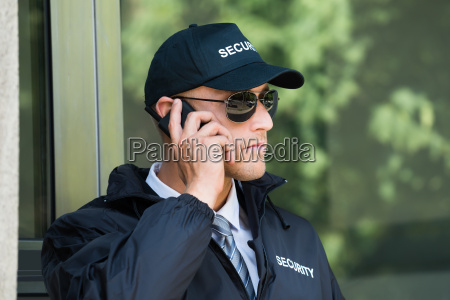 young security guard talking on walkie