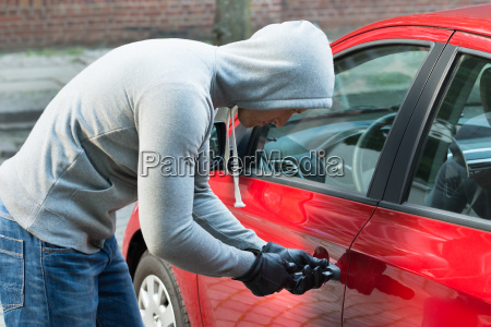 thief in hooded jacket stealing car