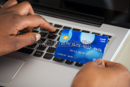 persons hand using debit card while