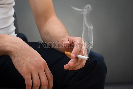 mittelteil des mannes haelt zigarette