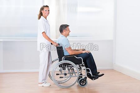 doktor pushing behinderten patienten auf dem