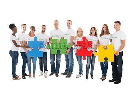 portrait of confident volunteers holding jigsaw