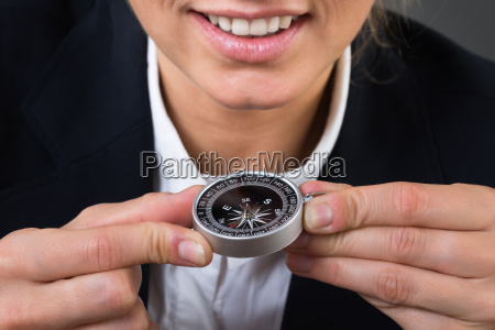 businesswoman holding compass over gray background