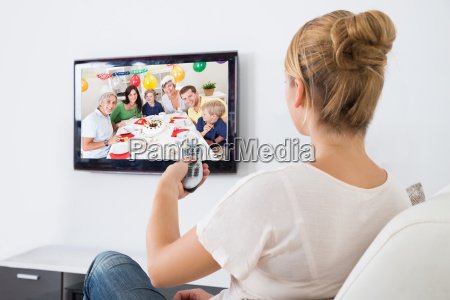 young woman watching television while sitting