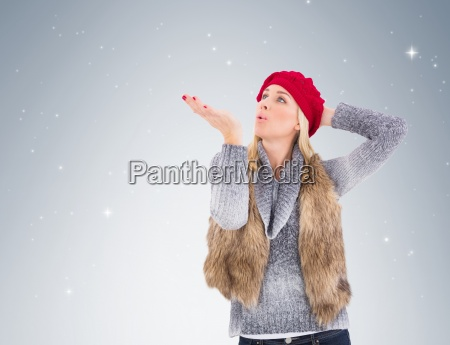 blonde in winter clothes blowing kiss