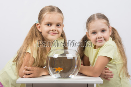 two girls sit at a round