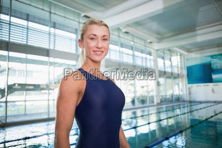 smiling female swimmer by pool at